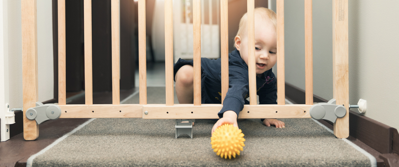 child-playing-behind-safety-gates-in-front-of-stairs-at-home