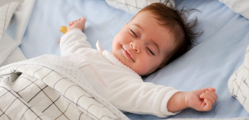 Smiling-baby-girl-lying-on-a-bed